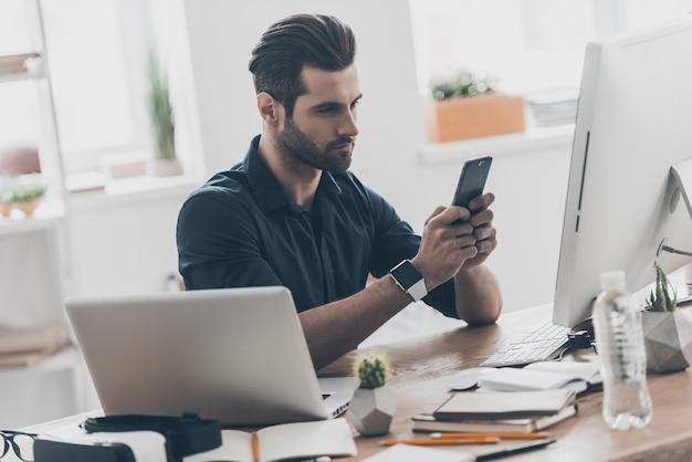 テキストメッセージは重要なメッセージです。クリエイティブオフィスの机に座って真面目な顔でメッセージを入力するハンサムな若い男