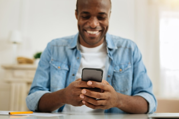 テキストメッセージ。魅力的な幸せな黒髪のアフリカ系アメリカ人男性がテーブルに座っている間、笑顔で彼の電話にメッセージを書いています