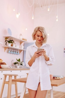 남자친구에게 문자를 보냅니다. 흰 셔츠를 입고 부엌에 서서 남자친구에게 문자를 보내는 젊은 여성