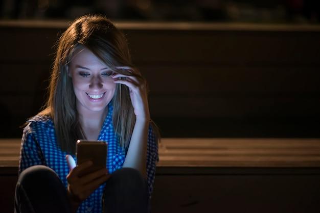 Женщина texting. макрофотография молодой счастливый улыбающийся веселый красивая женщина девушка, глядя на мобильный мобильный телефон, чтение отправки см. изолированные cityscape открытый фон. положительное выражение лица человеческие эмоции