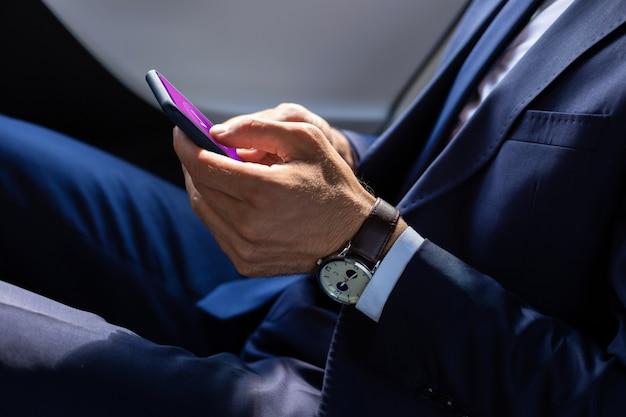 Текстовое сообщение другу. крупным планом бизнесмена носить ручные часы текстовых сообщений другу с помощью смартфона
