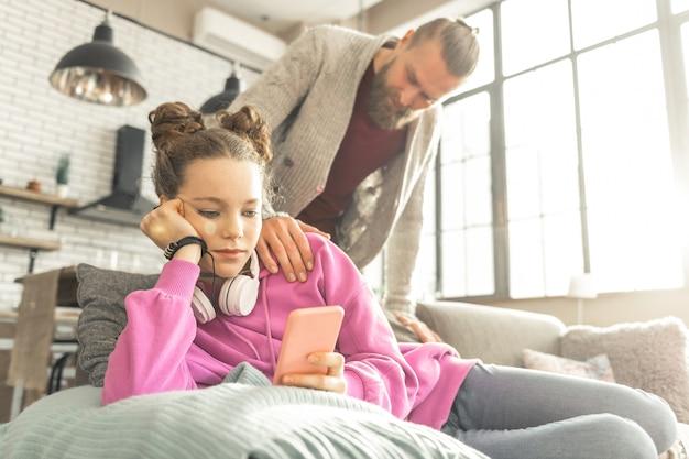 친구에게 문자 보내기. 아버지와 이야기하는 대신 친구에게 문자를 보내는 외로움을 느끼는 십대 소녀 스트레스