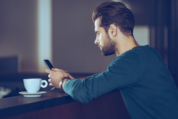 Texting to her. side view of handsome young man using his smart phone while sitting at bar counter