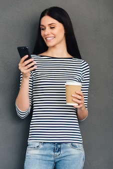 友人へのテキストメッセージ。コーヒーカップを持って立っている間彼女のスマートフォンを見ている魅力的な若い笑顔の女性