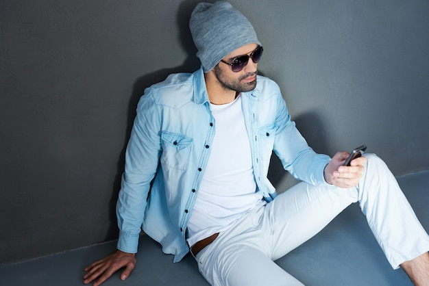 友人へのテキストメッセージ。灰色の背景に対して床に座っている間携帯電話を保持している眼鏡のハンサムな若い男の上面図