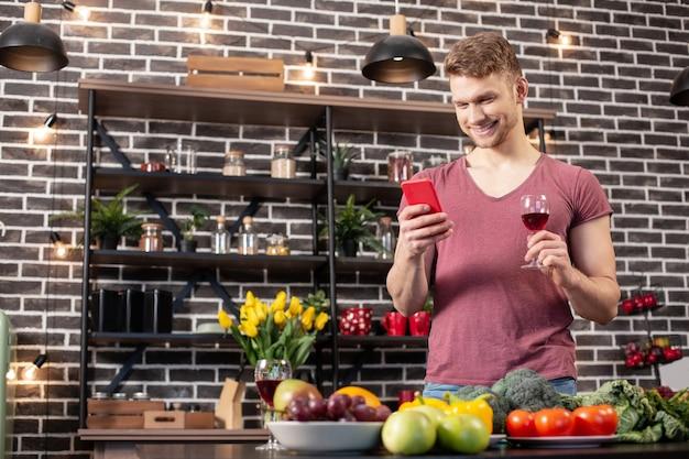아내에게 문자를 보냅니다. 청바지와 티셔츠를 입고 와인을 마시고 그의 아내에게 문자 메시지를 보내는 잘 생긴 blonde-haired 남자