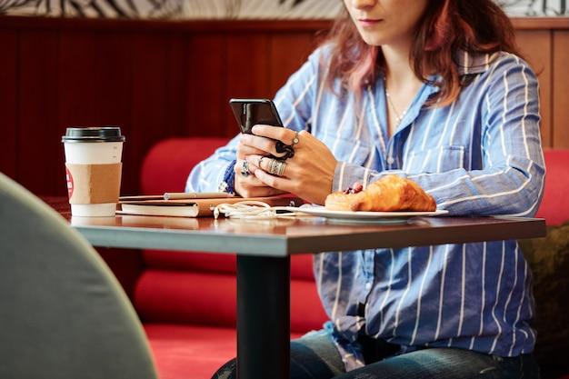 カフェのテーブルに座っているテキストメッセージの女性