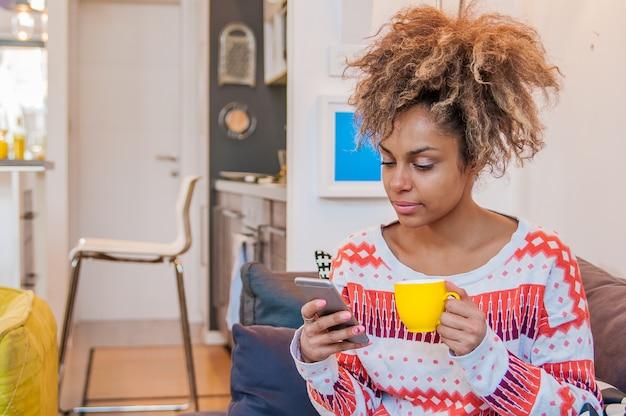 Портрет улыбается молодая черная женщина, сидя на диване у себя дома с мобильного телефона. красивая афроамериканец женщина с фризовой афро прическа texting на своем мобильном