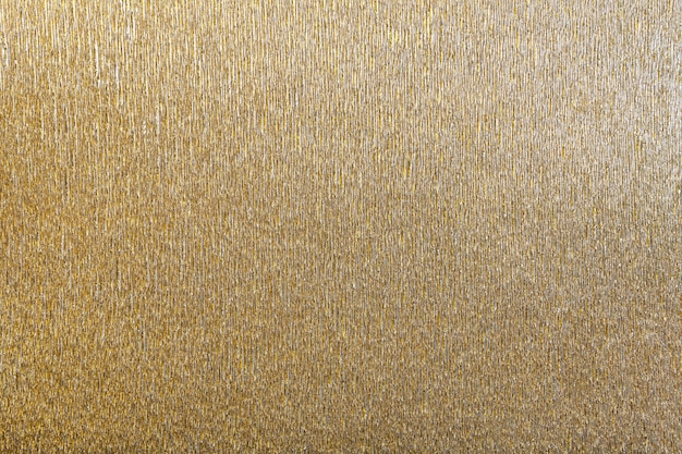 Textural of golden background of wavy corrugated paper, closeup.