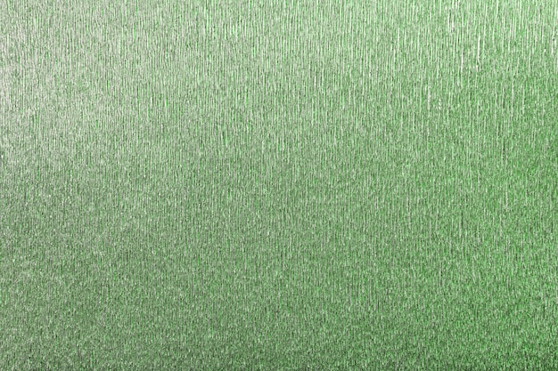 Textural of green background of wavy corrugated paper, closeup.