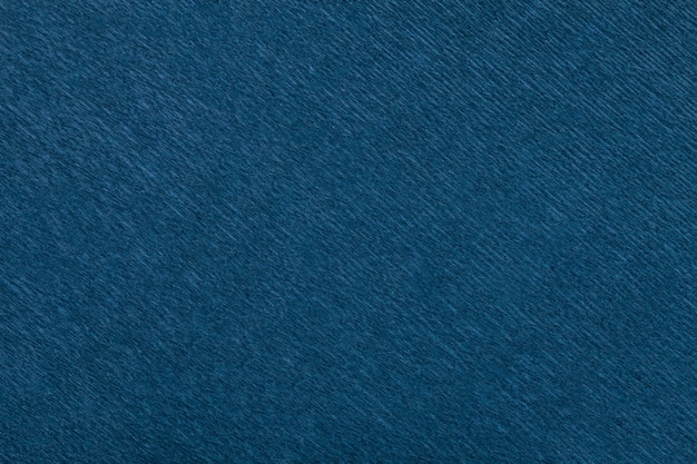 Textural of navy blue background of wavy corrugated paper, closeup