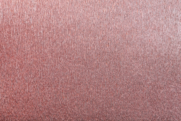 Textural of red background of wavy corrugated paper, closeup.