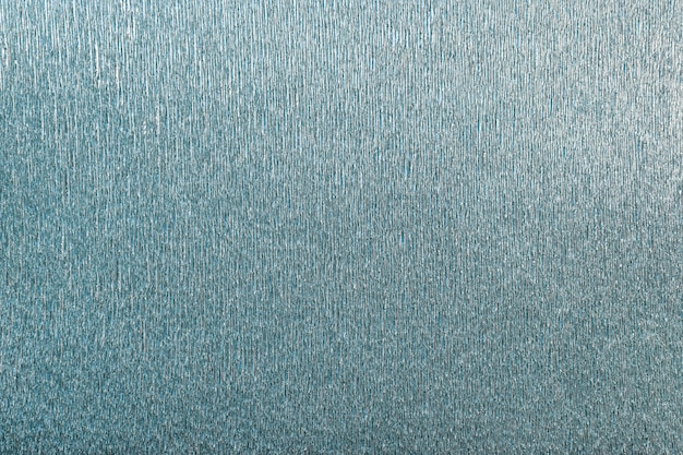 Textural of turquoise background of wavy corrugated paper, closeup.