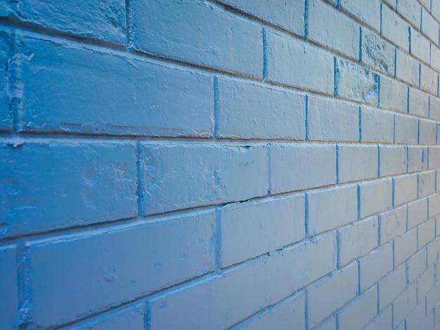 Текстура и фон голубой кирпичной стены против солнечного света.