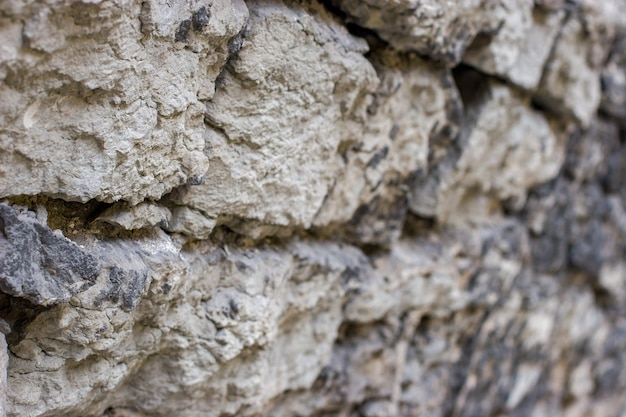 Предпосылка текстуры. античная каменная стена из натурального камня с селективным неглубоким фокусом в начале и размытой дистальной частью. серые камни кладут раствором.