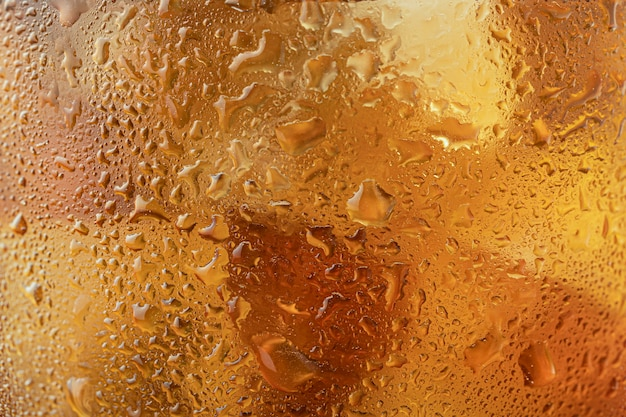 Texture background of a glass of golden whiskey or scotch close - up-drops and misted glass, blurred ice.