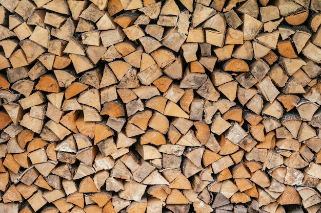 Texture background image of chopped firewood stacked in a woodpile, copy space