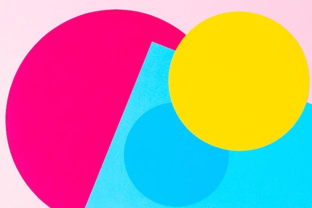 メンフィスジオメトリスタイルのファッションペーパーのテクスチャ背景。黄色、青、マゼンタ、ピンク色。トップビュー、フラットレイアウト