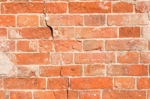 Texture background of old shabby brick wall with crack