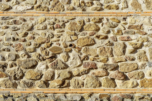 Texture background, old stone wall in sunny day with lines of bricks and large stones in medieval style. copy space for text. spain