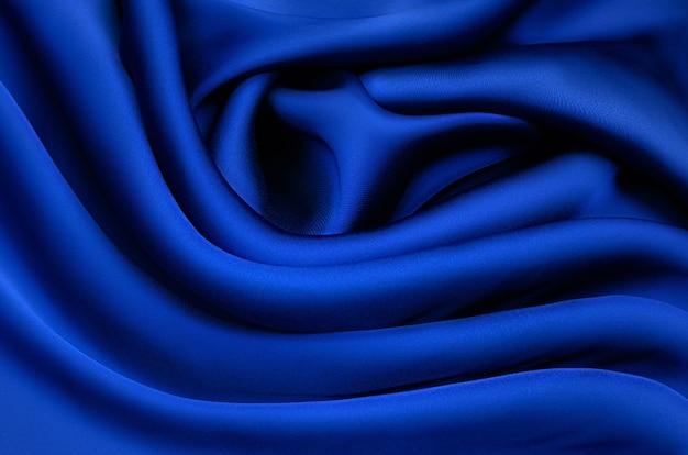 テクスチャ、背景、パターン。青い絹または綿またはウール生地の質感。生地の美しいパターン。