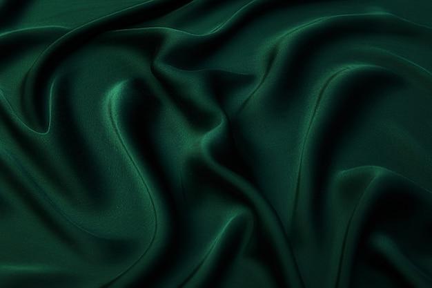 Текстура, фон, узор. текстура зеленой шелковой ткани. красивая изумрудно-зеленая мягкая шелковая ткань.