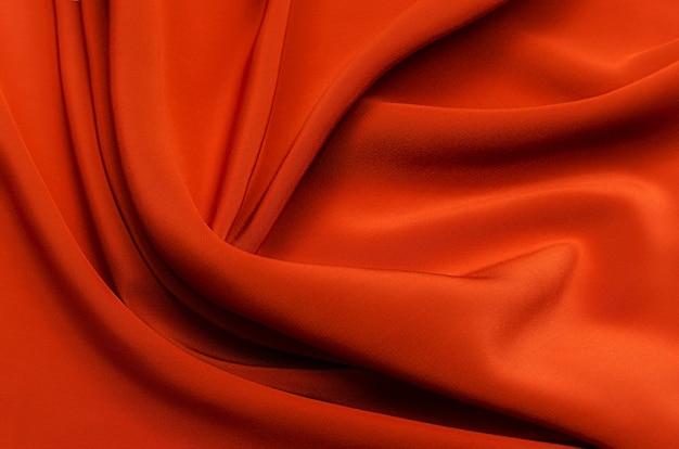 Текстура, фон, узор. текстура красного или оранжевого шелка, хлопка или шерсти. красивый узор из ткани.