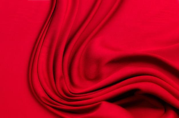 Текстура, фон, узор. текстура красного шелка или хлопчатобумажной или шерстяной ткани. красивый узор из ткани.