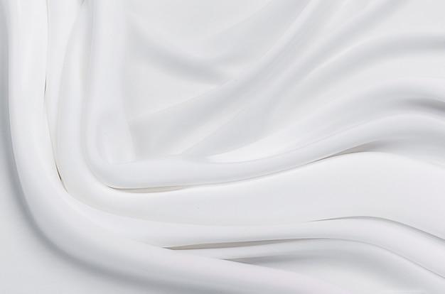 テクスチャ、背景、パターン。白またはアイボリーのシルクまたは綿またはウールの生地の質感。生地の美しいパターン。