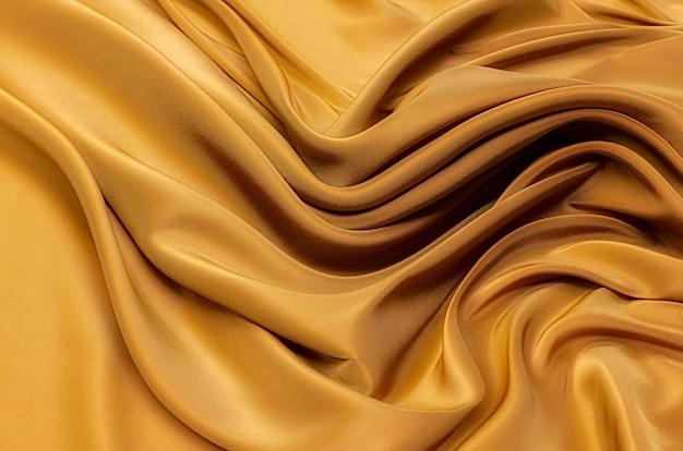 Текстура, фон, узор. текстура желтого или золотистого шелка, хлопка или шерсти. красивый узор из ткани.