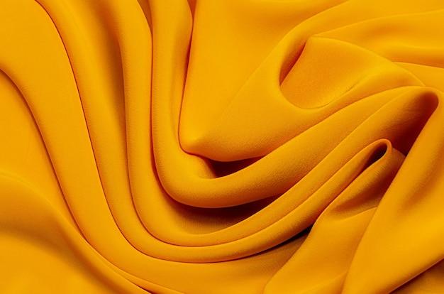 Текстура фоновый узор текстура желтого или золотистого шелка или хлопчатобумажной или шерстяной ткани