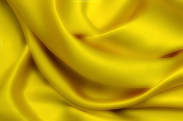 Текстура, фон, узор. текстура желтого шелка, хлопка или шерсти. красивый узор из ткани.