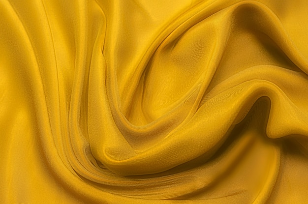 Texture, background, pattern. texture of yellow or golden silk or cotton or wool fabric. beautiful pattern of fabric.