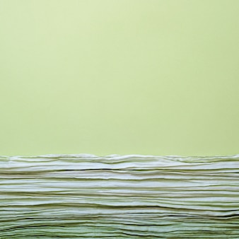 The texture of background picture the green corrugated fabric with parallel or diagonal folds on textured paper
