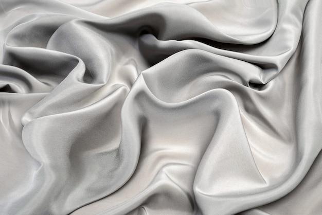 Текстура, фон, шелковая подкладка серая и белая ткань.
