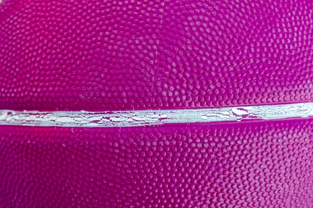Texture of a basketball ball with a violet color close up