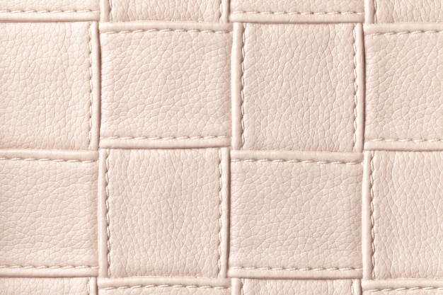 Texture of beige leather background with square pattern and stitch, macro. abstract from modern decorative light brown textile with geometric shape.
