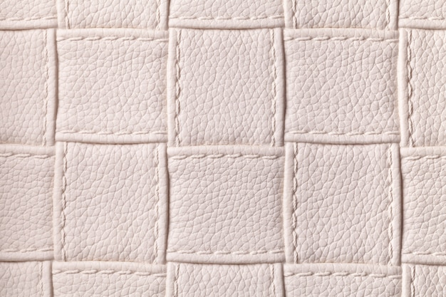 Texture of beige leather background with square pattern and stitch, macro.