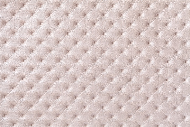 Texture of beige leather fabric background with capitone pattern. cream textile with chesterfield style.