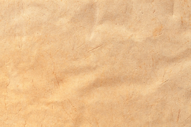 Texture of beige old paper, crumpled background. vintage brown surface. structure of craft cardboard.