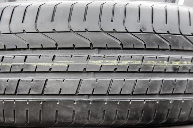 Texture of black tyre in car repair shop close up.