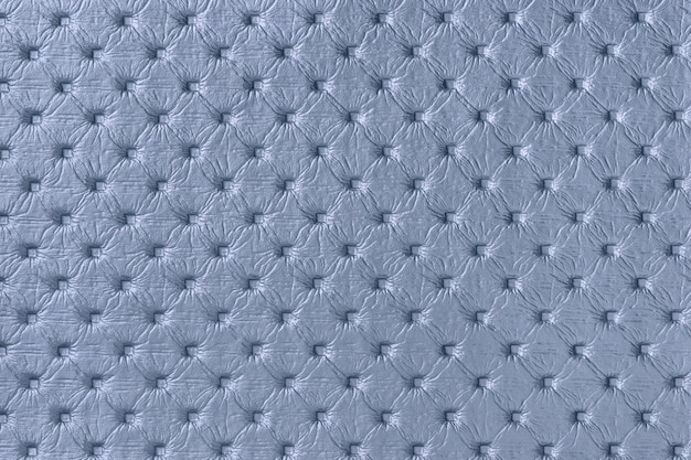 Texture of blue leather fabric background with capitone pattern. denim textile of retro chesterfield style.