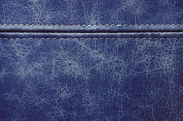 Текстура синяя кожа с горизонтальным декоративным швом, фон крупным планом