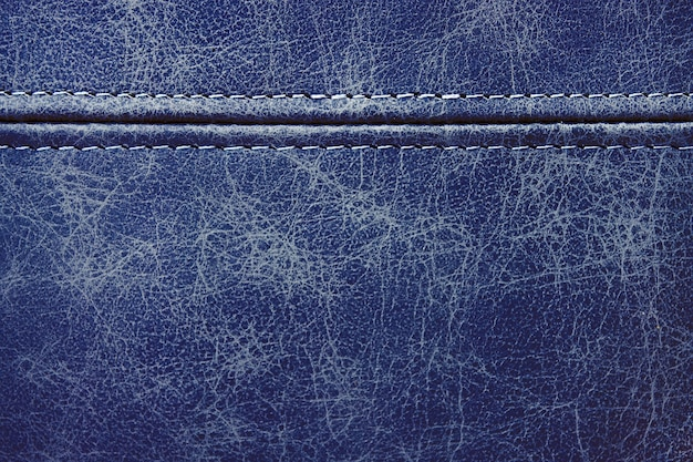 Texture blue leather with a horizontal decorative seam, closeup background