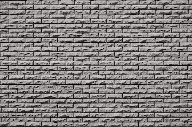 Texture of brick wall from relief stones under bright sunlight