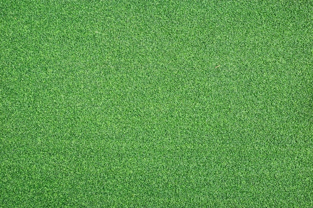 Texture of bright green artificial grass can use for background and design.