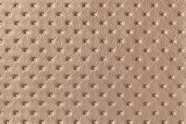 Texture of brown leather fabric background with capitone pattern, macro. bronze textile of chesterfield style.