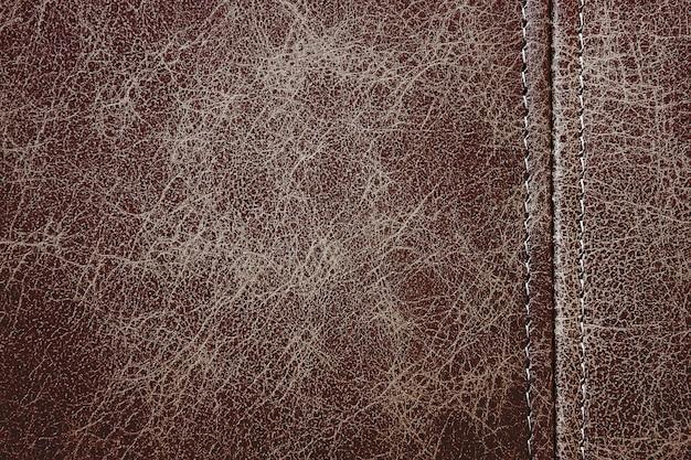 Текстура коричневой кожи с вертикальным декоративным швом, фон крупным планом