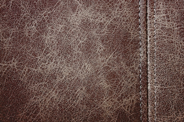 Texture brown leather with a vertical decorative seam, closeup background