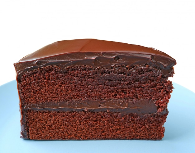 Texture of chocolate layer cake served on light blue plate isolated on white background
